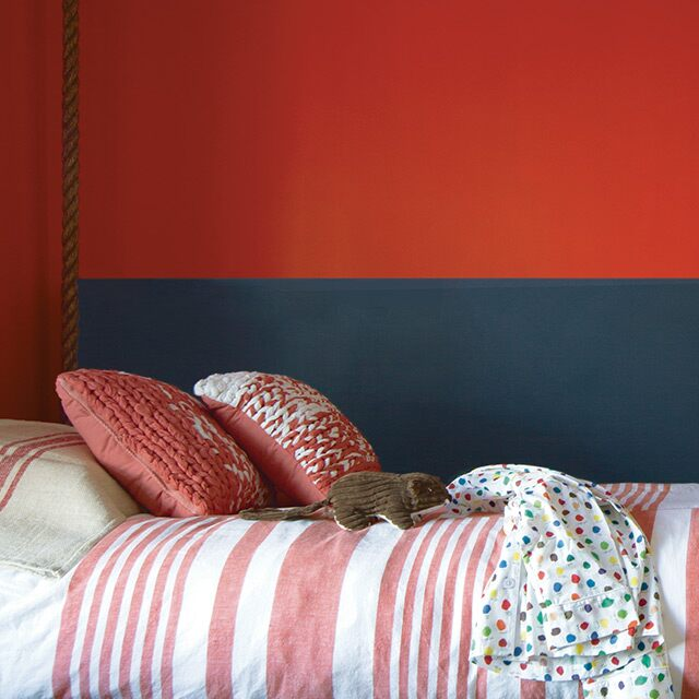 A floating bed raised with a sturdy rope bed frame sets a playful tone in a bold red, black and white kid's room.