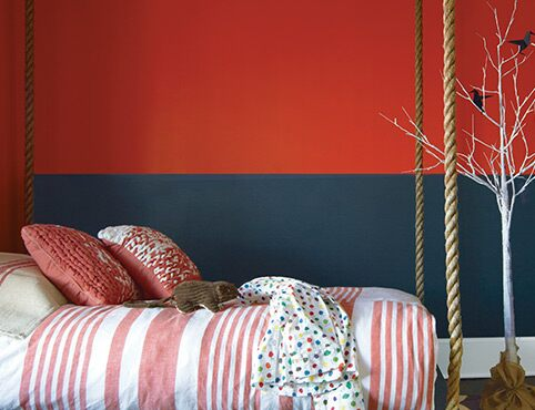 A kid's bedroom with a red and black painted wall features a swing bed.