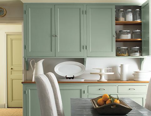 Light green cabinets add a soft glow as a backdrop to a dining table.