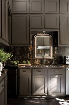 Rich brown kitchen cabinets, brown marble backsplash and an ornate mirror create a sumptuous culinary setting.