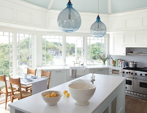 Bright, airy light blue kitchen with center island and cliffside view.