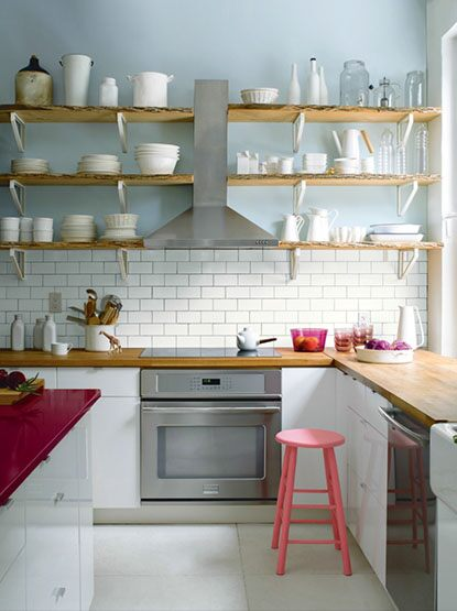 Clean, classic kitchen with red island and exposed shelves