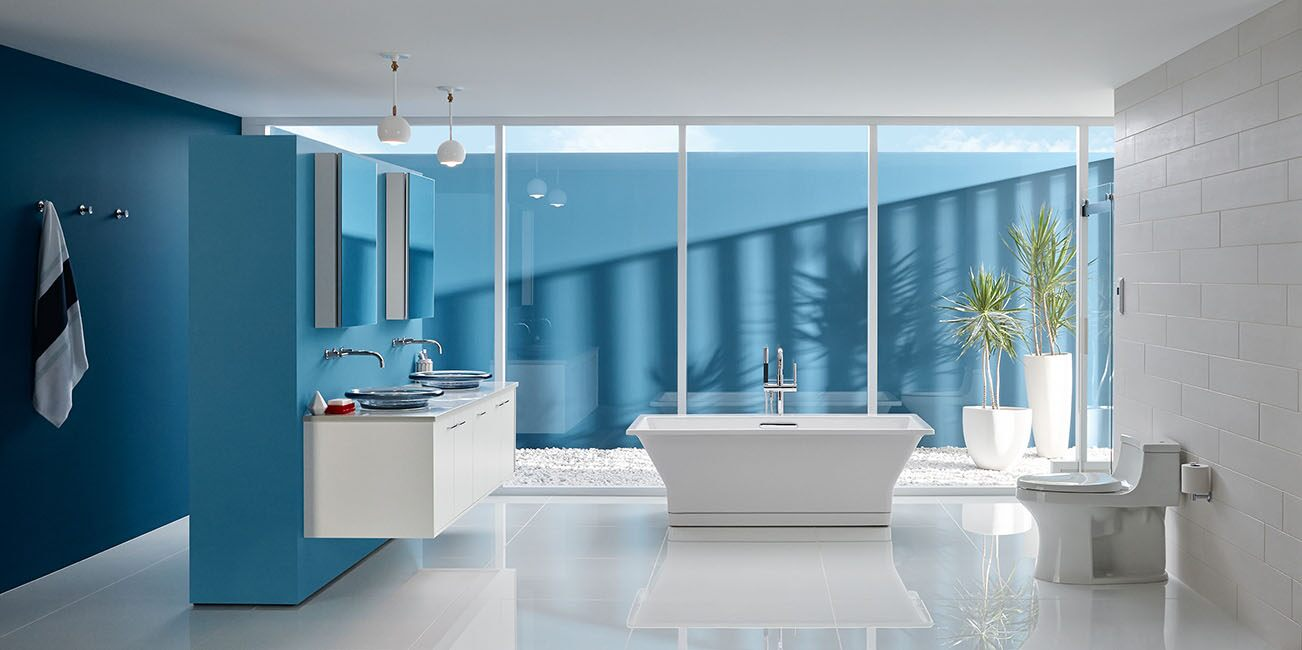 Blue master bathroom with Kohler finishes and large bathtub