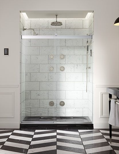 Marble shower with Kohler faucet and geometric floor patterns