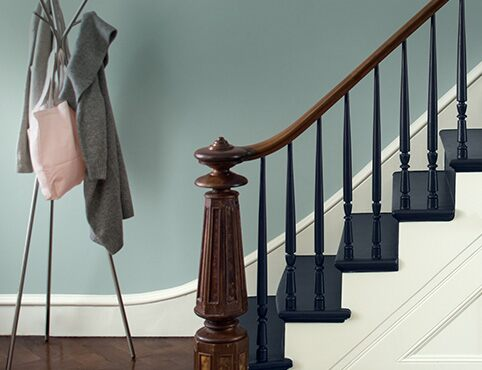 Entryway staircase with wood handrail, newel and navy-painted staircase.