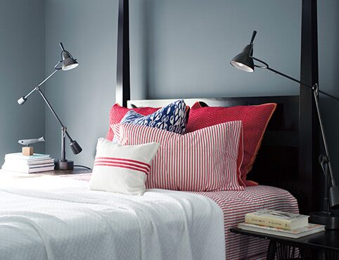 Sleek, Wolf Gray-painted bedroom with black bedframe, red and white bedding, two swing-arm lamps, and stacks of books.