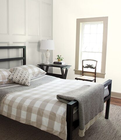 Relaxing bedroom with gray wainscoting behind black bed with gray and white checkered bedding.