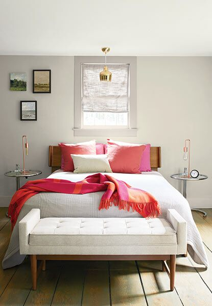 A relaxing bedroom with light gray walls, full size bed with pink pillows and a throw blanket, and cream bench.
