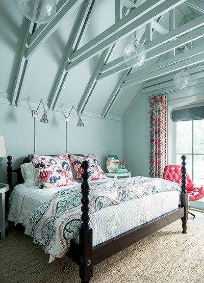 Vibrant blue bedroom with matching industrial ceiling including a large bed with printed bedding.