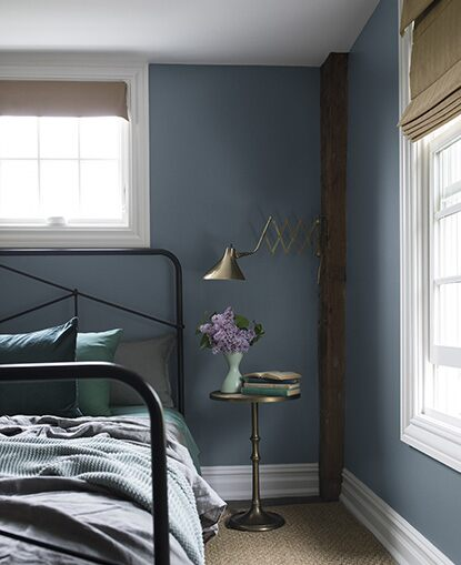 A blue bedroom painted in Black Pepper 2130-40 with exposed wood beams and a black-metal bed frame.