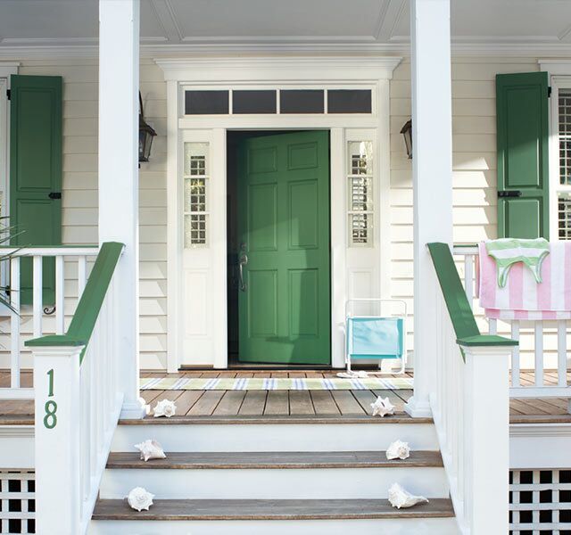 Green front door with matching window shutters.