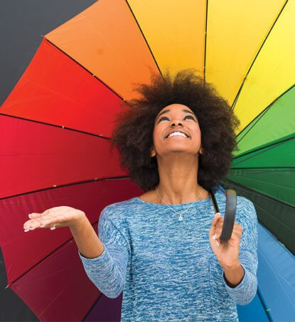 A woman stands under a multicolored umbrella
