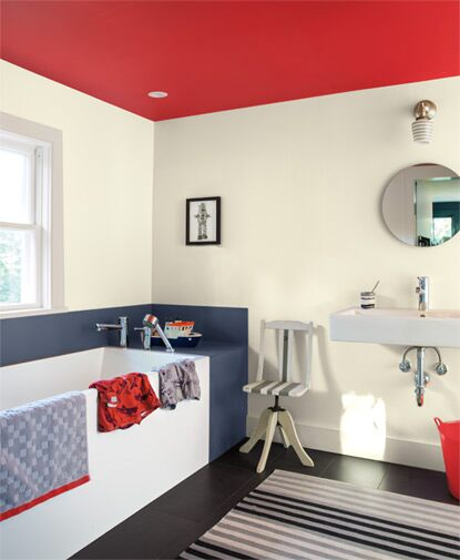 A  bathroom features a round mirror over a contemporary sink; black and white coloured walls and floors are accented by a red ceiling.