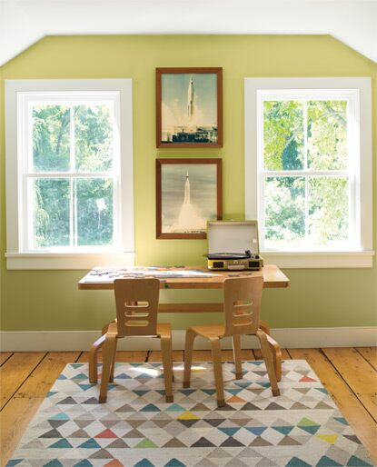 A kids' room with two windows features a portable turntable-topped desk set against a light green colour wall.