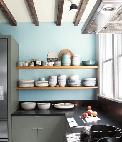 A residential kitchen with two exposed wooden shelves showcase bowls and plates against a light blue coloured wall.