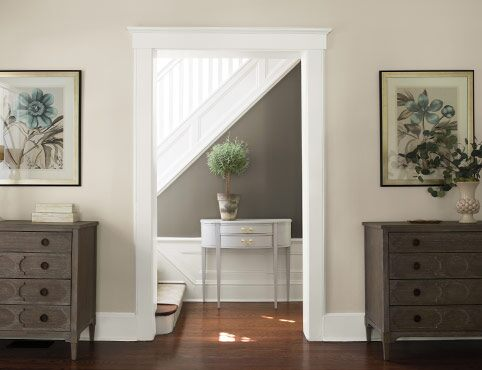 A gray and neutral hallway leads to a white staircase.