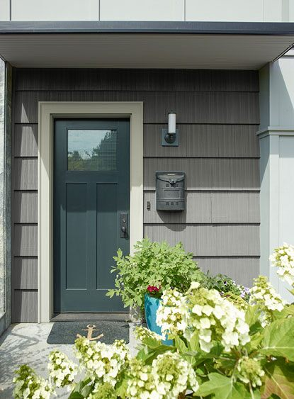 A front door in Knoxville Gray HC-160 and trimmed in Gray Owl OC-52 stands out against exterior siding painted in Storm AF-700.