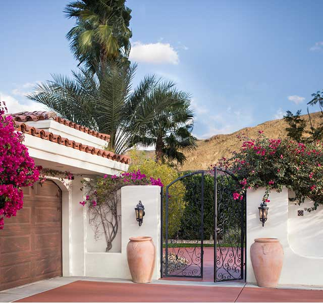 Gated driveway on a southwestern style home overlooking a scenic mountain range.
