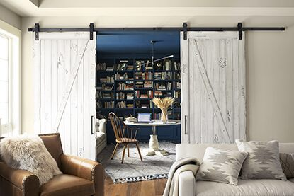 Sliding barn doors open to striking built-in blue bookshelf painted in Champion Cobalt 2061-20.