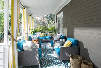Covered gray patio with white ceilings and matching gray furniture with blue cushions.