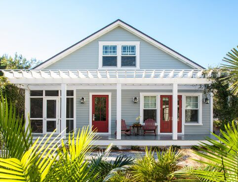 Sunny Southeast home painted in light blue-gray with red front doors in Caliente AF-290.