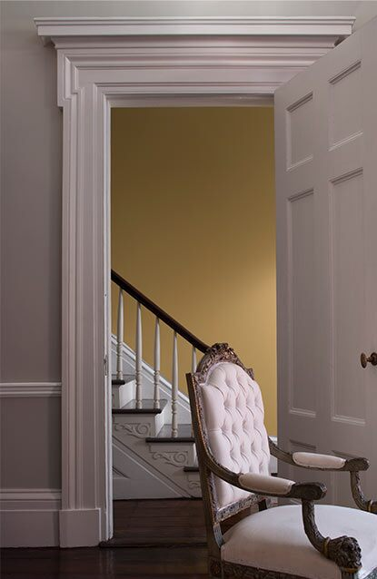 A living room in light gray features a door opening to a yellow-painted foyer.