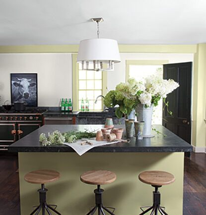 A modern green-painted kitchen with cut flowers and granite countertops.