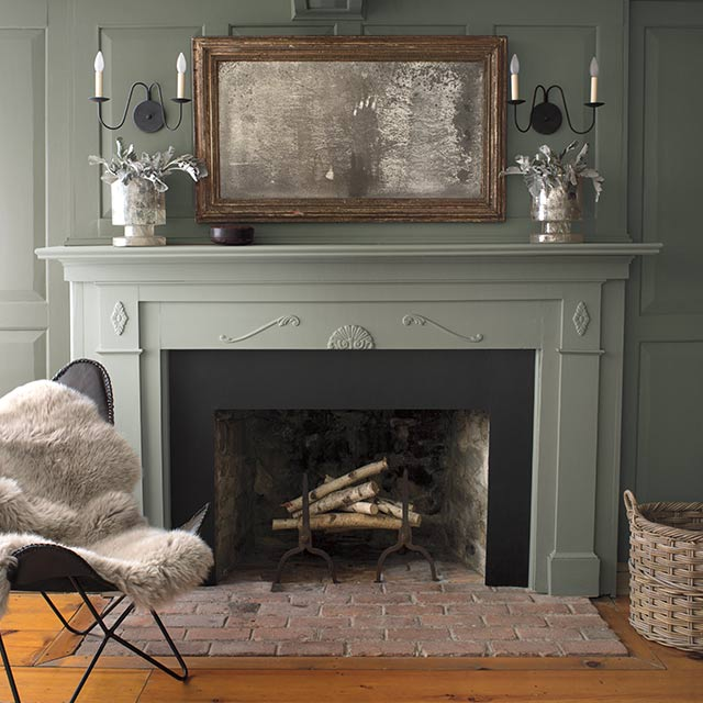 Olive green-painted walls with a light pink-painted ceiling and a muted green fireplace mantle.