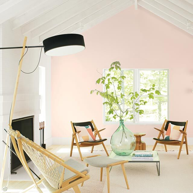 Vibrant living room with white beam ceilings and a light pink-painted accent wall featuring three chairs and a sofa.
