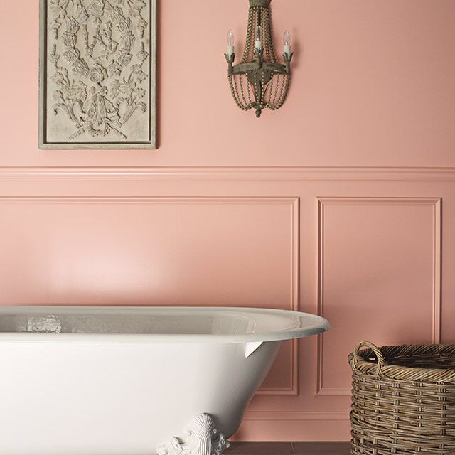 Bold pink-painted bathroom walls with matching wainscoting and a white clawfoot tub.