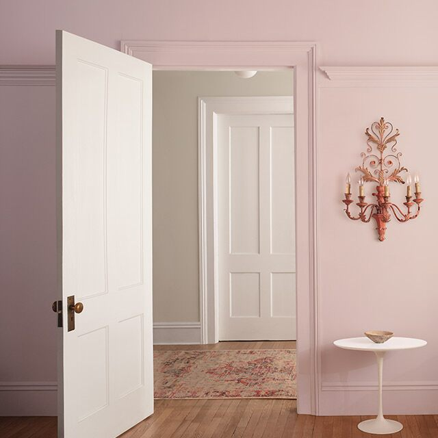 Light pink-painted walls with an open door leading out to a room with off-white-painted walls.