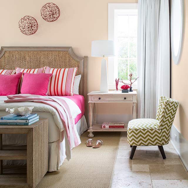 Peach-painted bedroom walls with a green chevron chair, side table, and bed featuring pink bedding.