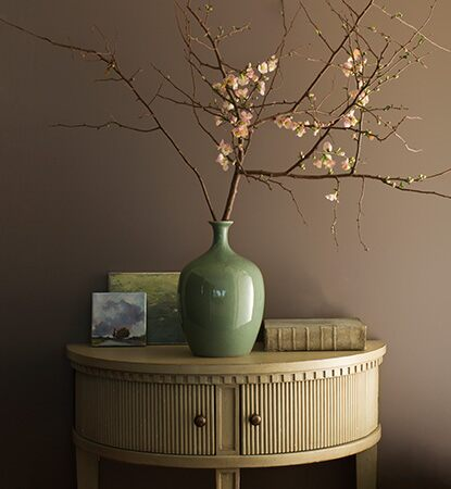 A painted hallway in taupe Weimaraner AF-155 with demi-lune table and jade vase holding flowering branches.