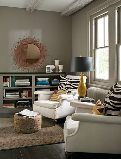 A cozy living room corner with two wing chairs and walls painted in Sparrow AF-720, a deep taupe colour.