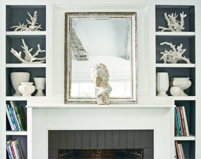 A white-painted fireplace is flanked by built-in shelving.