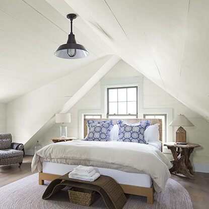 An off-white painted bedroom with rustic décor and sloped ceiling is flooded with light.