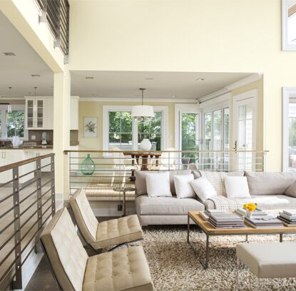 Bright and airy in creams and white paints, this high-ceiling family room is fresh and contemporary.