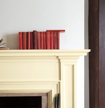 An off-white painted mantel against a cool white wall features red books.
