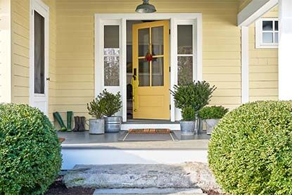 A bright and welcoming yellow front door painted in Stuart Gold HC-10.