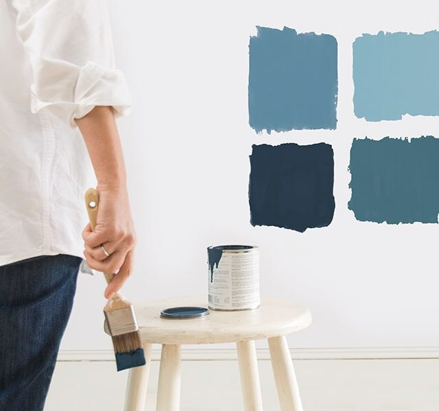 Painter sampling different interior blue paint colours.