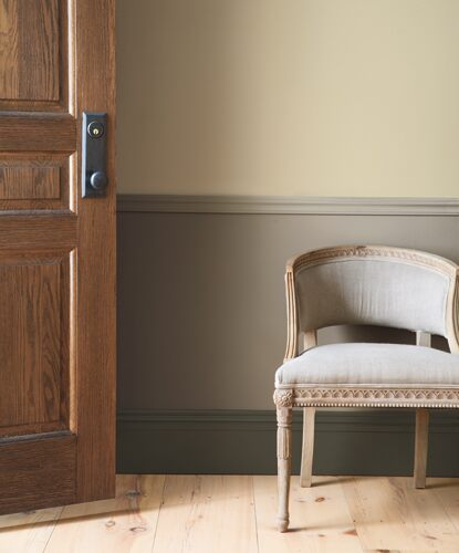An open wood door lets light in to a hallway featuring an antique accent chair set against earthy green-toned wainscotting.