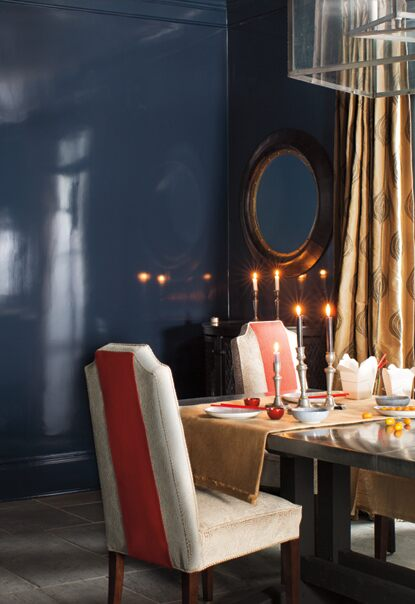 A luxurious dining room in dark blue walls features a glossy dining room table set with lit candlesticks and upholstered chairs with orange fabric accents.