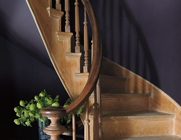Spiral wooden staircase with purple wall.