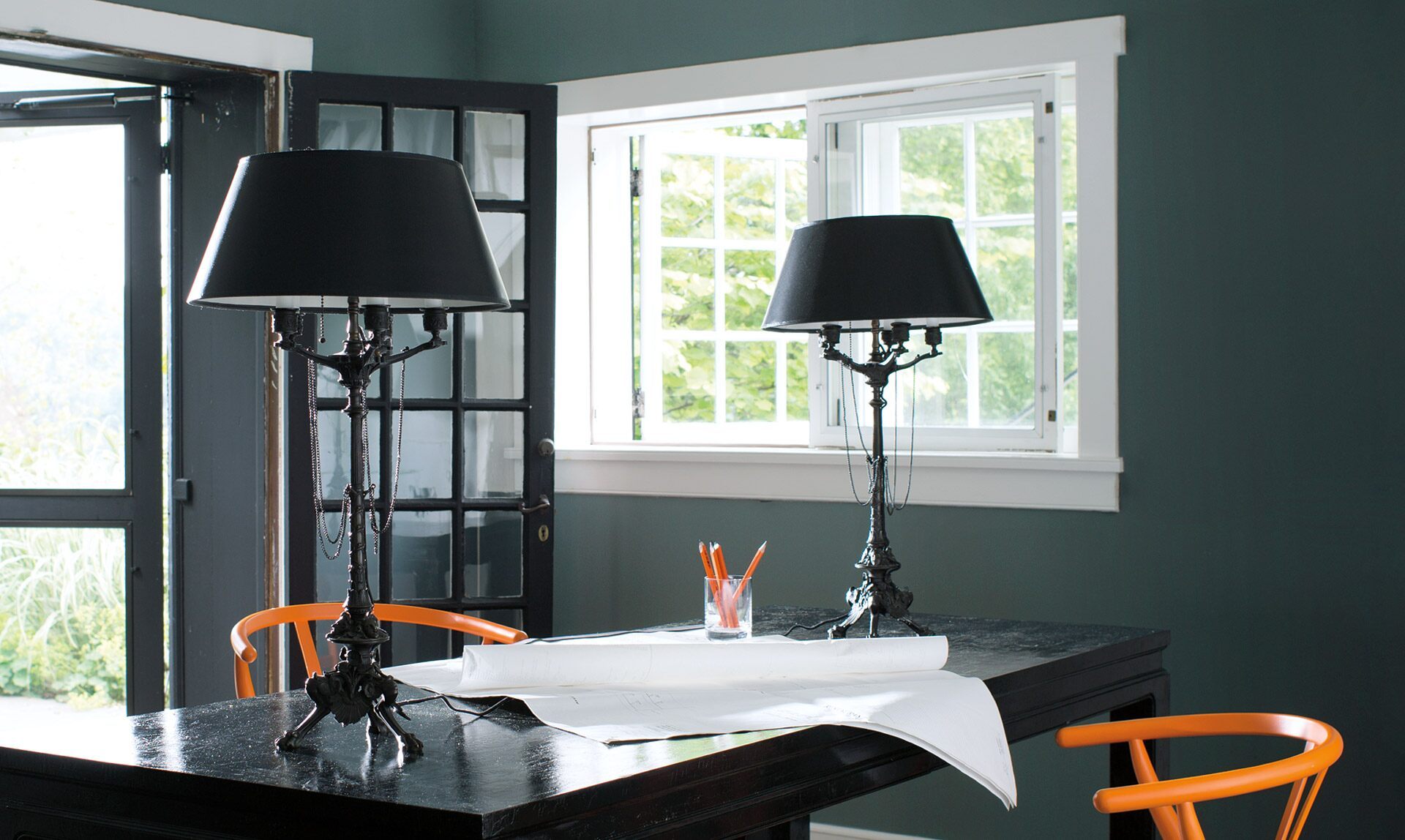 Contemporary home office with deep green walls, French doors and matching orange chairs