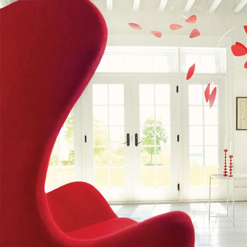 A red tulip chair faces a white room featuring a red mobile and French doors with views to greenery outside.