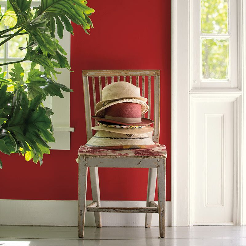 A pile of well-worn sunhats sits on a wooden chair against a red hallway wall next to an open front door.