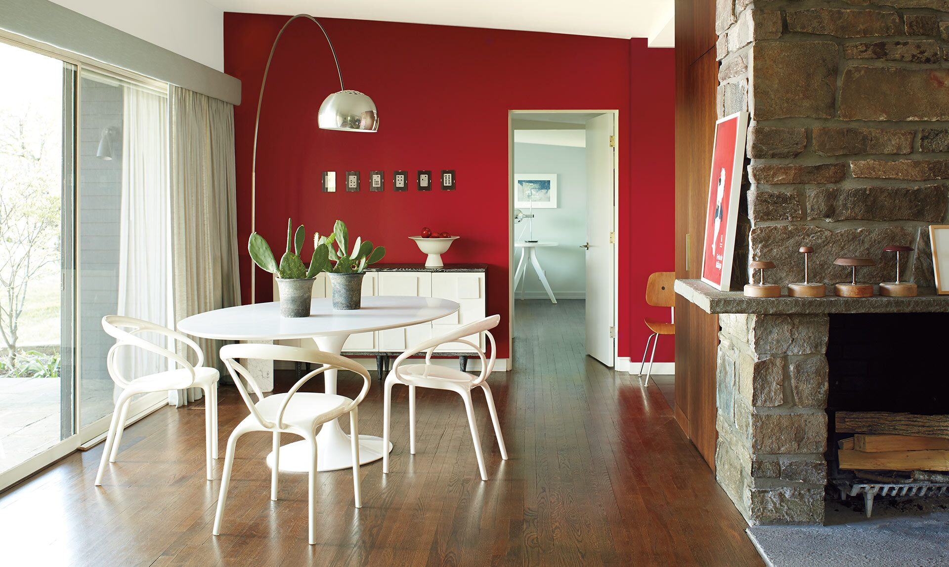 A contemporary dining room features a bold red accent wall with modern furnishings and fixtures.