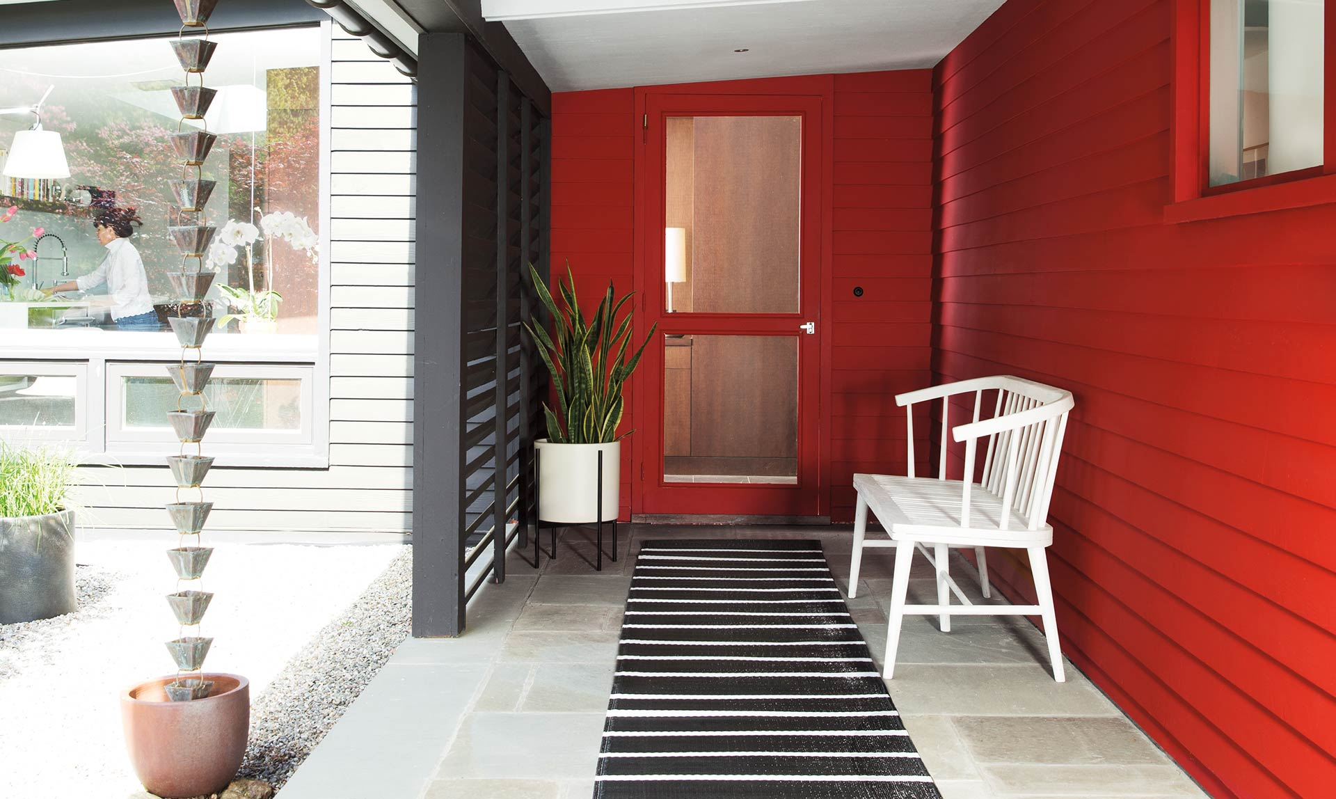 A semi-enclosed entryway with white wood bench against red shingled wall.
