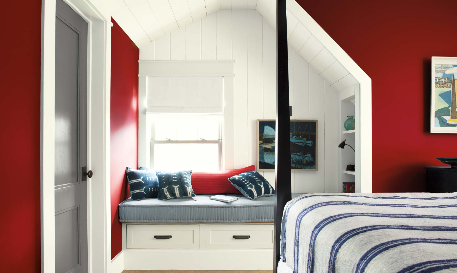 A cozy bedroom with built in cushioned bench features red walls and a poster bed.