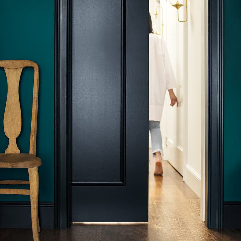 A deep blue-green-painted wall and navy-painted door opens to an off-white hallway. Colour of the Year 2019
